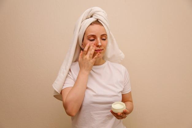 Kaukaska młoda kobieta w białej koszulki kładzenia twarzy śmietance na jej twarzy. pojęcie piękna.