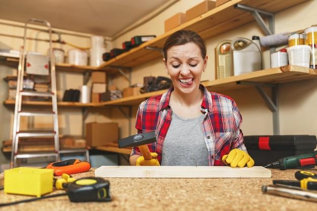 Kaukaska młoda kobieta w koszuli w kratę, szara koszulka, żółte rękawiczki pracująca w warsztacie stolarskim na drewnianym stole z różnymi narzędziami, wbijanie gwoździ w deskę młotkiem, wygięty gwóźdź.