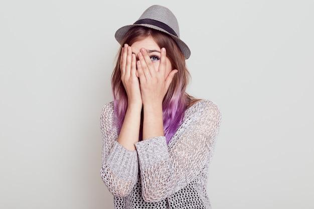 Kaukaska młoda kobieta zagląda przez palce, zakrywa twarz dłońmi, ubrana w kapelusz, czegoś się boi, patrząc rzucać palcami, na białym tle nad szarym tłem.