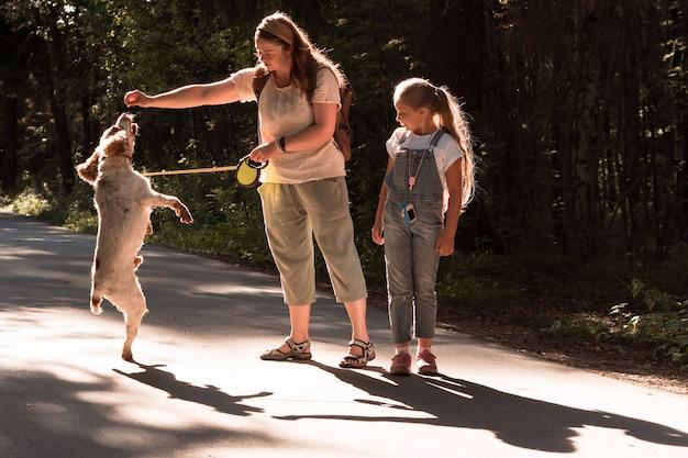 Kaukaska młoda matka i córka spacerują i trenują psa w parku miejskim