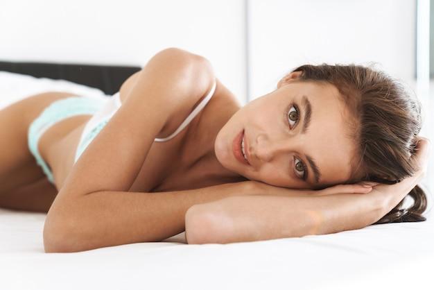 Kaukaska młoda piękna kobieta nosi koronkową bieliznę leżącą na białej pościeli w domu