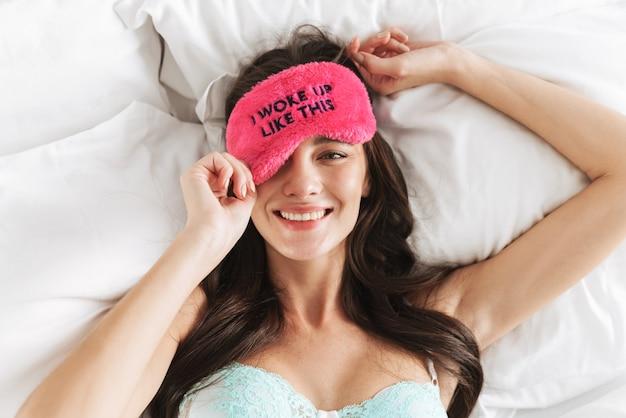 Kaukaska młoda piękna kobieta ubrana w bieliznę i maskę do spania leżącą w łóżku w domu