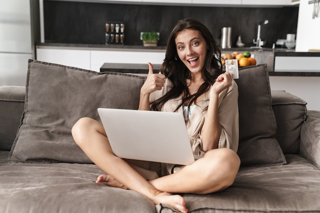 Kaukaska młoda piękna kobieta w ubraniach wypoczynkowych, korzystająca z laptopa i karty kredytowej na kanapie w domu