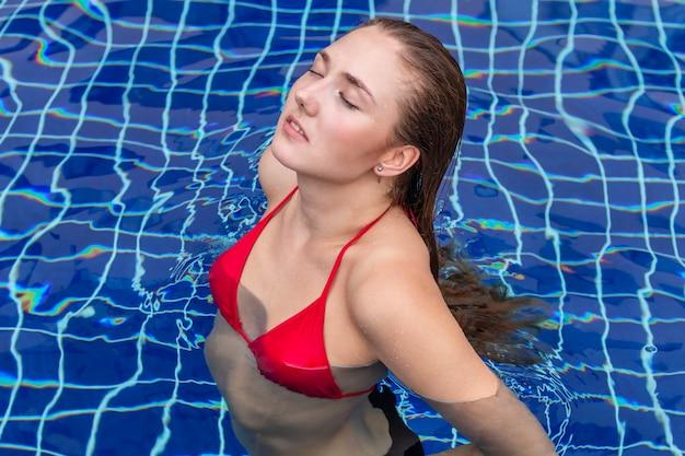 Kaukaska mody kobiety pozycja w pływackim basenie.