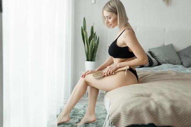 Kaukaska pani siedzi w domu na łóżku, trzymając suchą szczotkę w górnej części nogi zabieg na cellulit, oczyszczanie skóry suchej.