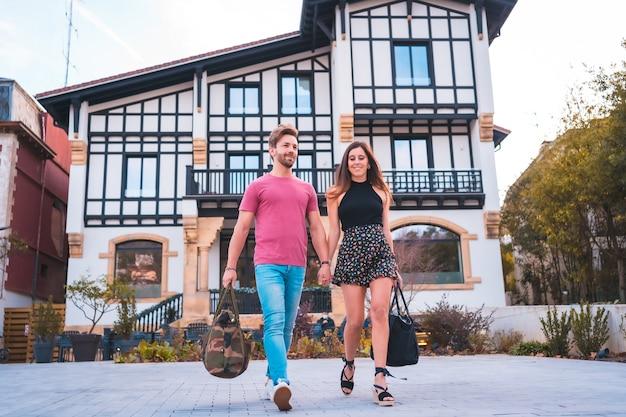 Kaukaska para opuszczająca hotel po wspaniałych wakacjach. letni styl życia
