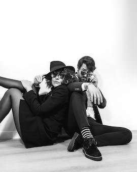 Kaukaska para siedzi na podłodze w czarno-białej sesji mody, ubrana w stylowe garnitury i okulary przeciwsłoneczne