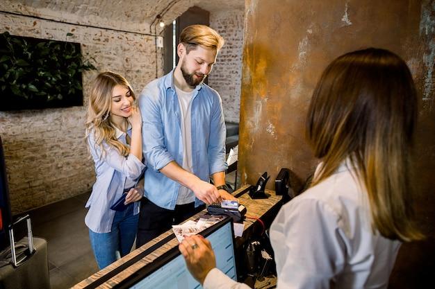 Kaukaska para w podróży robi zameldowaniu w hotelu. dobiera się dawać karcie kredytowej recepcjonista przy kontuarem w hotelu