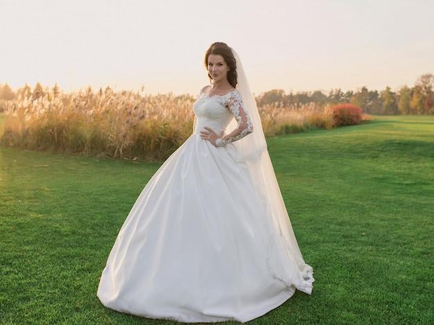 Kaukaska piękna kobieta panna młoda w tradycyjnej europejskiej białej sukni stojącej na boisku