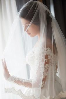 Kaukaska piękna kobieta panna młoda w tradycyjnej europejskiej białej sukni stojącej przy oknie