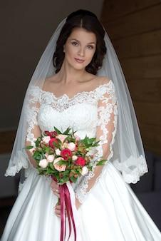 Kaukaska piękna kobieta panna młoda w tradycyjnej europejskiej białej sukni z bukietem ślubnym