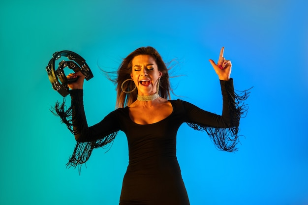 Kaukaska piosenkarka z tamburynem na niebieskim tle studia w świetle neonowym