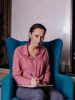 Kaukaska psycholog siedzi na krześle w gabinecie i patrzy w kamerę