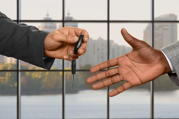 Kaukaska ręka biznesmena dająca klucz. przekazywanie kluczyków do samochodu w ciągu dnia. co moje jest twoje. powiedz nie transportowi publicznemu.