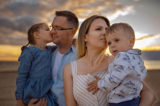 Kaukaska rodzina cieszy się zachodem słońca na plaży latem