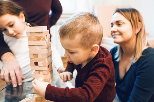 Kaukaska rodzina uczy swojego małego blond syna grać jengę w weekendowy dzień