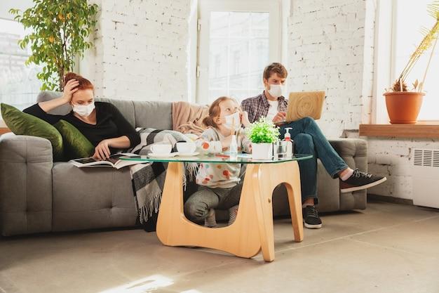 Kaukaska rodzina w maseczkach i rękawiczkach izolowana w domu z objawami oddechowymi koronawirusa, takimi jak gorączka, ból głowy, kaszel w stanie łagodnym.