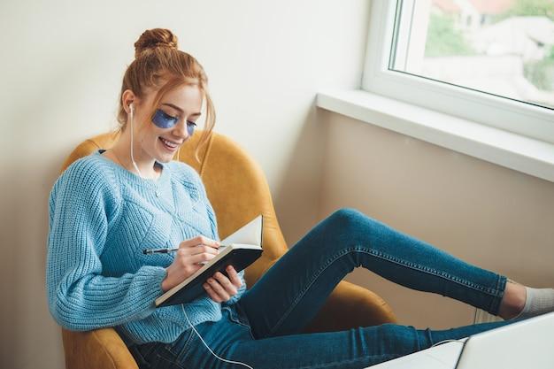 Kaukaska ruda dama z piegami w hydrożelowych opaskach na oczy, uśmiechająca się i pisząca w książce