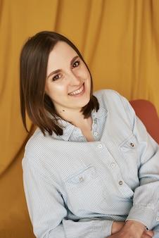 Kaukaska rudowłosa kobieta w swobodnej niebieskiej koszuli uśmiecha się na żółtym tle