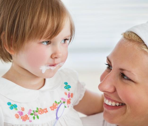 Kaukaska śliczna dziewczyna szczotkuje jej zęby z jej matką