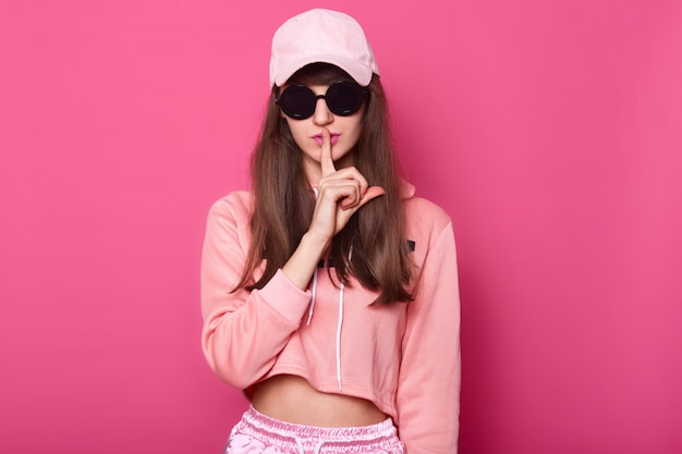 Kaukaska szczupła młoda dziewczyna nastolatka w jasnej skróconej bluzie z kapturem pozuje na różowo, trzyma palec przed ustami, prosząc o ciszę. ciii, sekret.