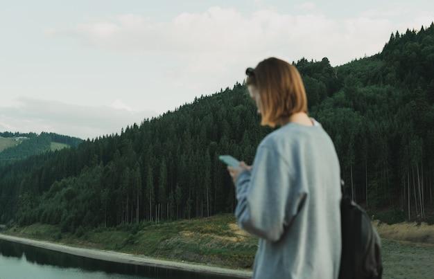 Kaukaska turystka korzystająca z aplikacji na smartfona z mapami, aby znaleźć drogę do lasów iglastych