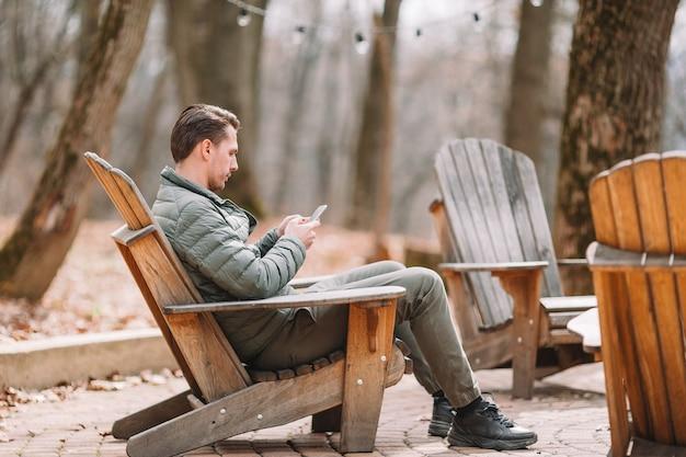 Kaukaska turystyczna chłopiec z telefonem komórkowym outdoors w kawiarni. człowiek za pomocą smartfona.