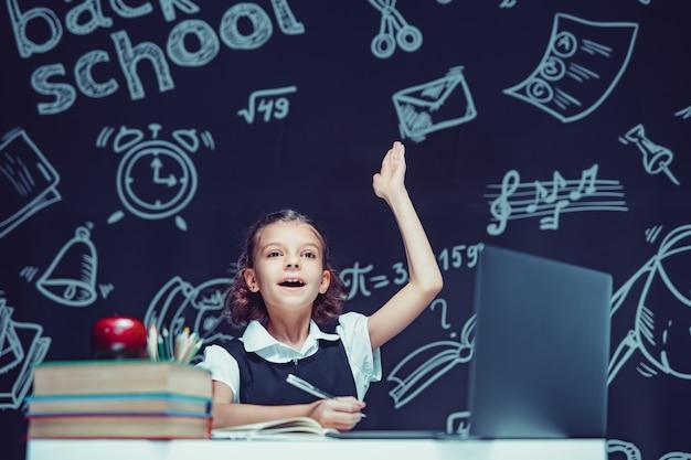 Kaukaska uczennica podnosi rękę, siada przy laptopie podczas lekcji online, nauka na odległość w szkole
