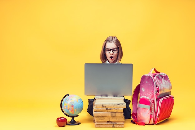 Kaukaska uczennica w szoku siedzi za stosem książek, patrząc na laptopa, edukacja dzieci
