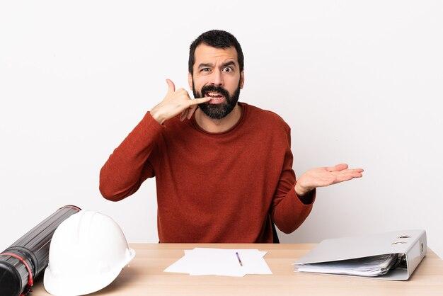 Kaukaski architekt mężczyzna z brodą w tabeli czyniąc gest telefonu i wątpi.