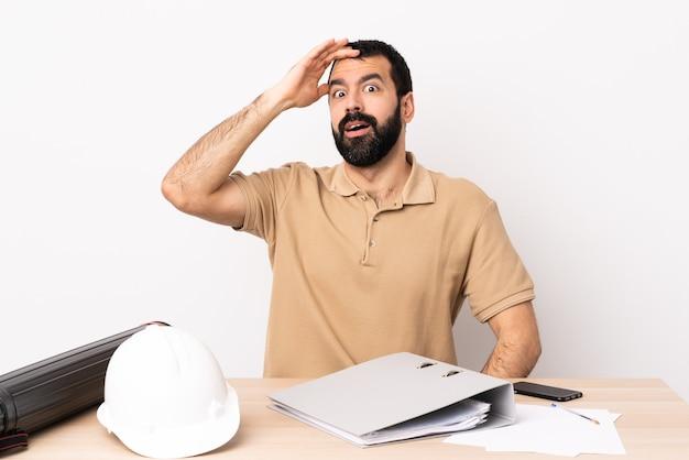 Kaukaski architekt mężczyzna z brodą w tabeli robi gest niespodzianki, patrząc w bok.