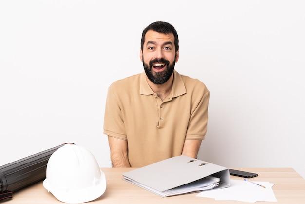 Kaukaski architekt mężczyzna z brodą w tabeli z zaskoczeniem wyraz twarzy