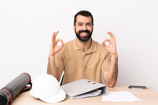 Kaukaski architekta mężczyzna z brodą w stole pokazuje ok znaka z dwiema rękami