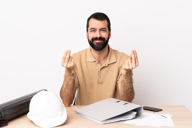 Kaukaski architekta mężczyzna z brodą w stole robi pieniądze gestowi