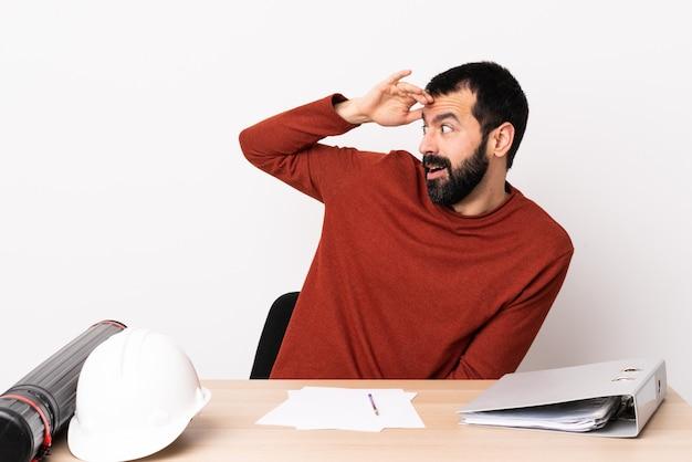 Kaukaski architekta mężczyzna z brodą w stole z niespodzianki wyrażeniem podczas gdy patrzejący stronę