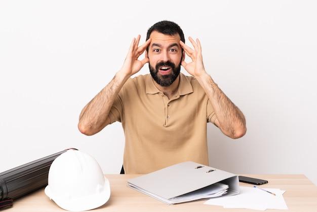 Kaukaski architekta mężczyzna z brodą w stole z niespodzianki wyrażeniem