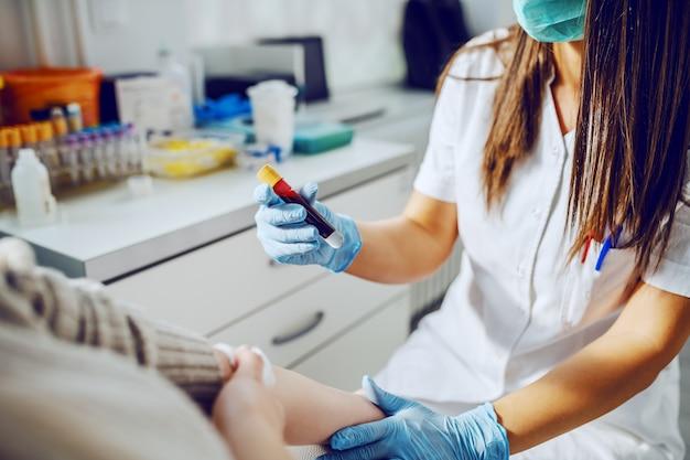 Kaukaski asystent laboratoryjny w mundurze, z maską i gumowymi rękawiczkami, trzymający probówkę z krwią, podczas gdy pacjent siedzi i trzyma absorbującą bawełnę.