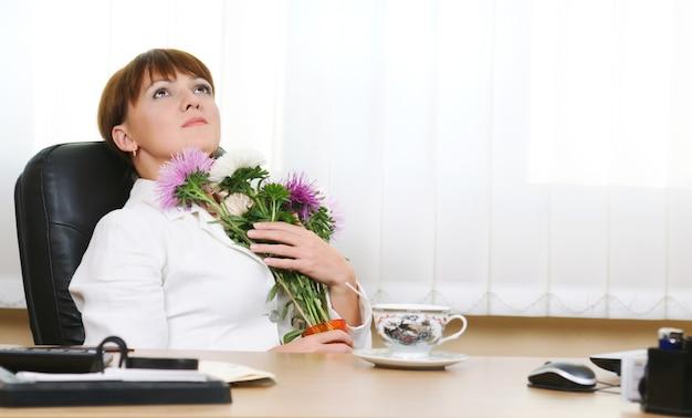 Kaukaski biały brunetka kobieta siedzi przy biurku przytulanie bukiet kwiatów. kubek, mysz komputerowa, folder dokumentów na stole. jasne tło