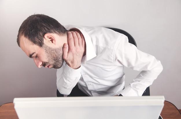 Kaukaski biznesmen cierpi na ból szyi w biurze.