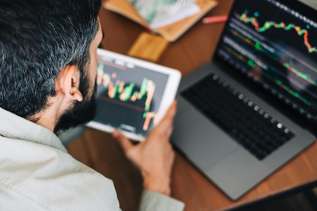 Kaukaski biznesmen handlujący online, korzystający z technologii komputerowej, patrzący na handel giełdowy i analizujący
