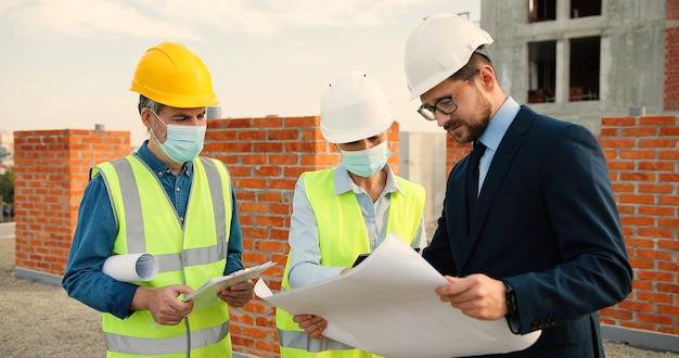 Kaukaski biznesmen i kilka konstruktorów płci męskiej i żeńskiej patrząc na projekt planu budynku w kaskach i maskach medycznych. inżynier i konstruktorzy rozmawiają o konstrukcjach.