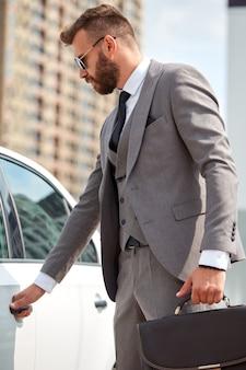 Kaukaski biznesmen w formalnej odzieży, otwierając drzwi swojego reprezentatywnego samochodu