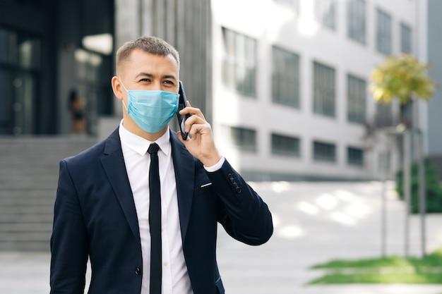 Kaukaski biznesmen w masce medycznej rozmawia przez telefon