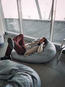 Kaukaski biznesmen z brodą czeka na swój lot na lotnisku i rozmawia przez telefon w pozycji leżącej
