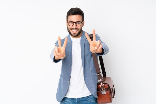 Kaukaski biznesowy mężczyzna odizolowywający na biel ścianie uśmiecha się zwycięstwo znaka i pokazuje