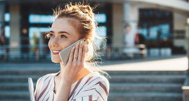 Kaukaski bizneswoman z piegami i rudymi włosami rozmawia przez telefon podczas spaceru na zewnątrz