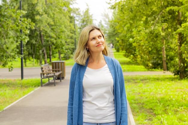 Kaukaski blond kobieta spaceruje wśród zielonych drzew wzdłuż ścieżki i patrzy w górę. uśmiechy, pozytywne emocje. spacerować w parku. oddychać świeżym powietrzem. inspekcja przyrody. zadowolony wygląd