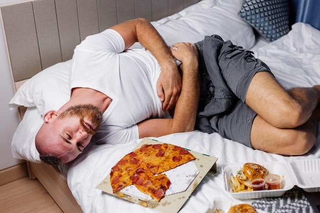 Kaukaski brodaty mężczyzna leży na złej po przesadnej pizzy fast food i hamburgerach