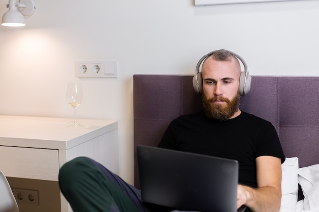 Kaukaski brodaty mężczyzna w słuchawkach w sypialni na łóżku pracuje na laptopie w domu, wpisując, myśląc.