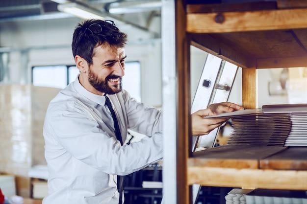 Kaukaski brodaty przełożony biorąc płytę drukarską stojąc w drukarni.